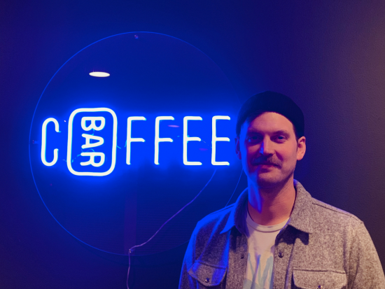 This is a picture of Kyle Anderson the founder of Coffee Bar Seattle. He is a white man wearing a black beanie and has a brown mustache. Behind him is a neon blue sign that says Coffee Bar.