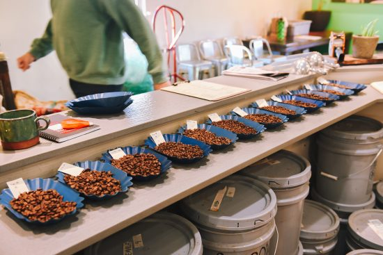 A wide angle shot of roasted coffee samples. They sit in small blue plates.