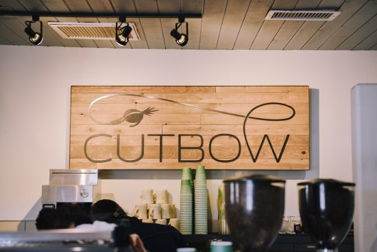 A shot of the cafe sign that read cutbow. We see the top of an espresso hopper and several to-go cup stacks in the back.