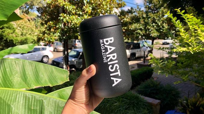 Una mano sosteniendo una taza negra para llevar con el logo de la revista Barista.