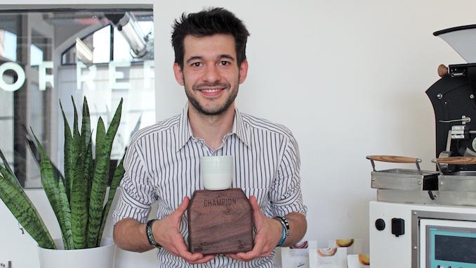 Alessandro es un hombre blanco italiano que se sienta sonriendo y sostiene una placa con su trofeo Latte Art Champion.