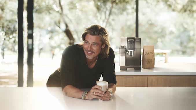 El actor Brad Pitt sonríe sobre un mostrador y sostiene una taza de café con leche en la mano.  La máquina de café espresso DeLonghi está detrás de él.