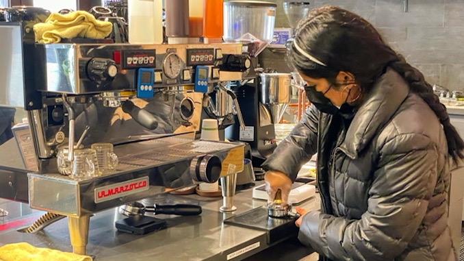 Un barista con una chaqueta gris de puff está parado frente a una máquina de café expreso y está llenando un trago de café.
