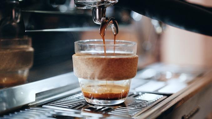 Una taza de cerámica de vidrio KeepCup se encuentra debajo de una máquina de café exprés que sirve café.
