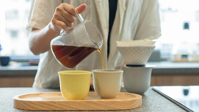 La mitad inferior del cuerpo vierte café en tazas en una bandeja.