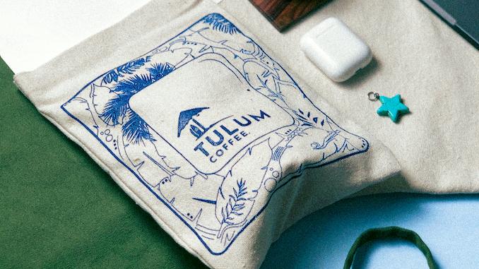 Una bolsa de tela contiene granos de café con el logo de Tulum.