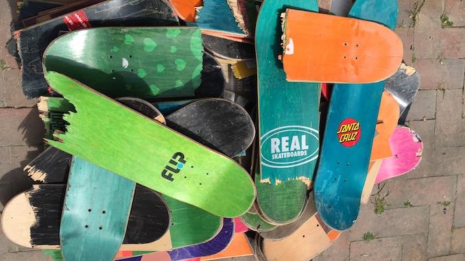 Un puñado de patinetas de colores usados sentados en una pila en el suelo.