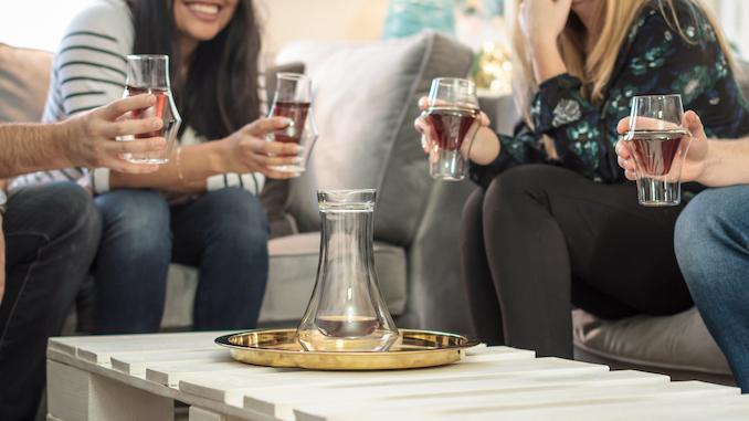 Las mitades inferiores de cuatro personas sostienen vasos de café Kruve.